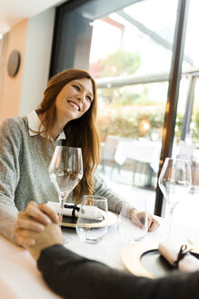 Smiling woman holding hands with man in a restaurant - VABF01683