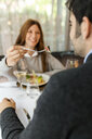 Smiling woman letting man taste the food in a restaurant - VABF01686