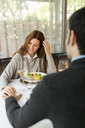 Smiling woman holding hands with man in a restaurant - VABF01689