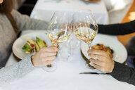 Close-up of couple clinking wine glasses in a restaurant - VABF01692