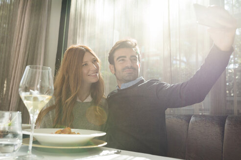 Smiling couple taking a selfie in a restaurant - VABF01695