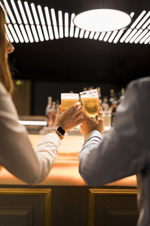 Close-up of couple clinking beer glasses in a bar - VABF01707