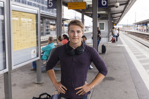 Young man with hands on hips, standing at rail station in Aschaffenburg, Germany - TCF05958