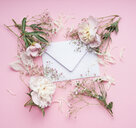 Studio shot of a white envelope framed by flowers on a pink background - INGF06918