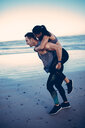 Fit adult couple doing piggyback on a beach - INGF07109