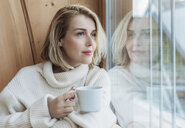 Woman holding coffee cup while looking through window at home - CAVF54097