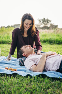 Smiling husband relaxing on wife's lap against clear sky at park - CAVF54139