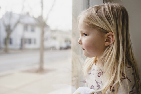 Close-up of girl sitting by window at home - CAVF54175