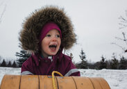 Girl screaming while sitting on sled against sky during winter - CAVF54184