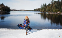 Boy wrapped in blanket walking on snow covered field by lake against sky - CAVF54187