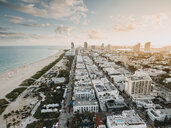 Aerial view of cityscape by sea against cloudy sky during sunset - CAVF54199