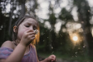 Playful girl blowing dandelion on field - CAVF54217