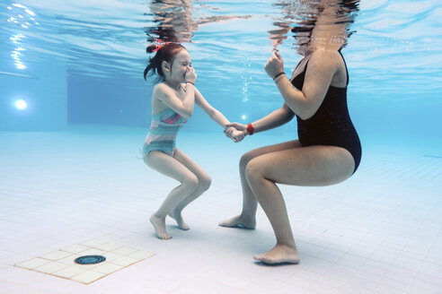 Low section of mother with daughter swimming underwater in pool - CAVF54250