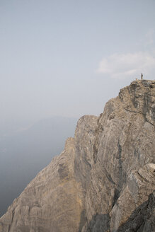 Distant view of male hiker standing on cliff against sky - CAVF54253