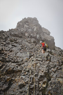 Low angle view of sporty hiker climbing mountain against sky - CAVF54262