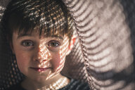Close-up portrait of cute boy under fabric at home - CAVF54340