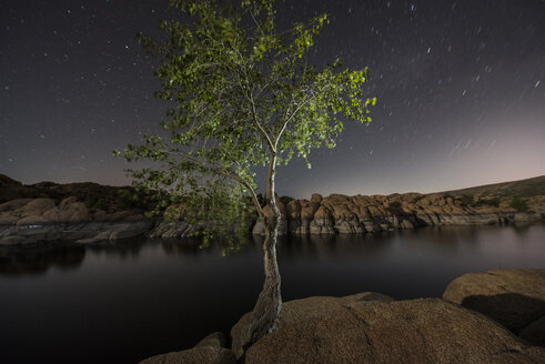 Watson Lake by rock formations against star field - CAVF54352