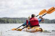 Rear view of senior couple kayaking on lake against cloudy sky - CAVF54355
