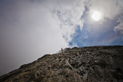 Mid distance view of hiker climbing rock formations against cloudy sky - CAVF54364