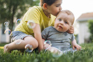 Boy kissing brother while sitting on grassy field at back yard - CAVF54382