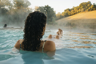 Rear view of woman relaxing in thermal pool - CAVF54385