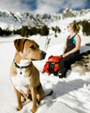 Female hiker and dog sitting on snowy field against mountains - CAVF54391