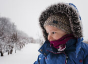 Girl in warm clothing standing on snow covered field against sky - CAVF54397