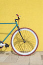 Bicycle parked against yellow wall at sidewalk in city - CAVF54409