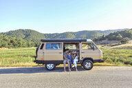 Family sitting in van against clear sky - CAVF54415