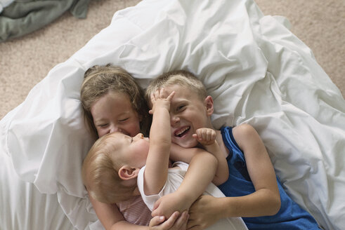High angle view of happy siblings lying on bed at home - CAVF54427