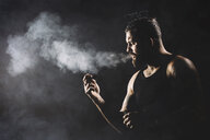 Man smoking while standing against black background - CAVF54460