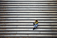High angle view of woman sitting on steps at park - CAVF54469