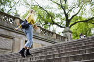 Low angle view of woman climbing steps at park - CAVF54475