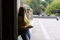 Woman leaning on wall at park - CAVF54481