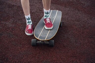 Woman's legs in socks and sneakers standing on carver skateboard - VPIF00971