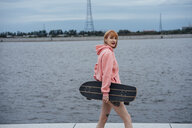 Young woman holding carver skateboard walking at the riverside - VPIF00980