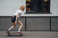 Young woman riding carver skateboard on the sidewalk - VPIF01007