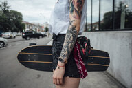 Close-up of young woman holding carver skateboard on the pavement - VPIF01025
