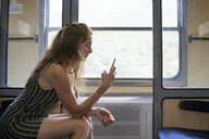 Bulgaria, red-haired woman using smartphone, sitting in train - AFVF01945