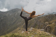 Red-haired woman doing yoga on top of a mountain, lord of the dance - AFVF01948
