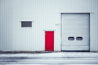 Minimalist shot of a closed red door in the snow - INGF07234