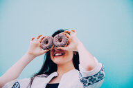 Head shot of woman making funny face with chocolate donuts - INGF07273