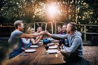 Young group of adults toasting at a table during sunset - INGF07318