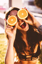 Close-up of woman holding sliced oranges - INGF07459