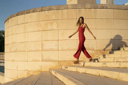 Spain, Barcelona, Montjuic, young woman wearing red jumpsuit walking on stairs - AFVF01955
