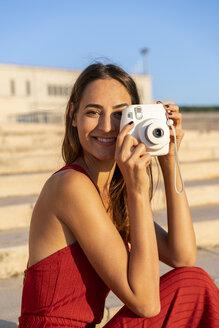 Portrait of smiling young woman taking instant photo outdoors - AFVF01958