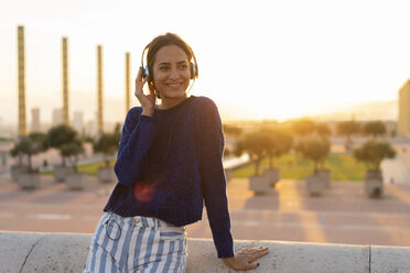 Spain, Barcelona, Montjuic, smiling young woman listening to music with headphones at sunset - AFVF01967