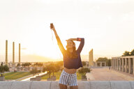 Spain, Barcelona, Montjuic, happy young woman listening to music with headphones at sunset - AFVF01973