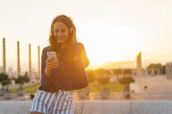 Spain, Barcelona, Montjuic, smiling young woman with cell phone and headphones at sunset - AFVF01976