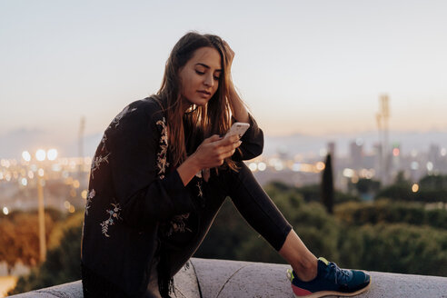 Spain, Barcelona, Montjuic, young woman sitting on a wall at dusk using cell phone - AFVF01985